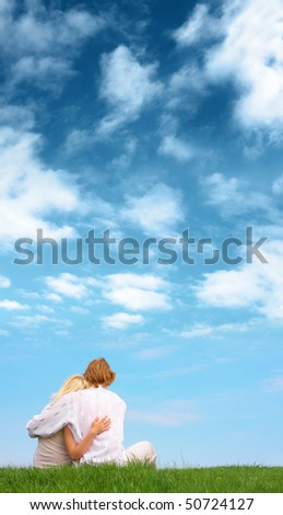 Guy and girl sitting on the ground beneath the cloudy sky