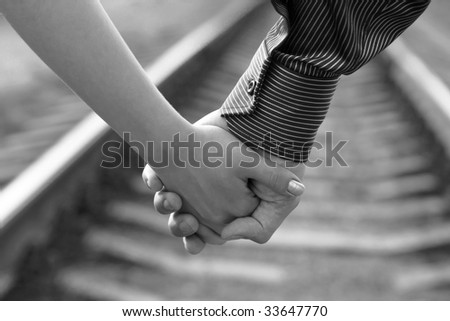 Guy and girl walking hand by hand along railroad