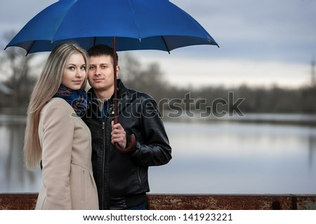 Guy and the girl under an umbrella on the bridge