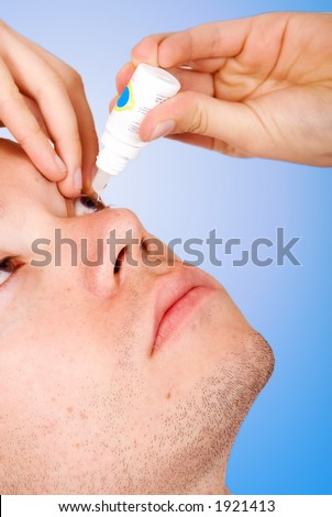 guy applying eye drops to his eye, focus is on face