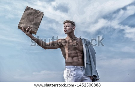 Guy attractive macho carry shopping bag made out of brown paper. Eco package. Sales season. Shop assistant concept. Man muscular athlete hold shopping bag sky background. Hot sales and discount.