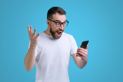 Guy being happy winning a bet in online sport gambling application on his mobile phone. Isolated over blue background.
