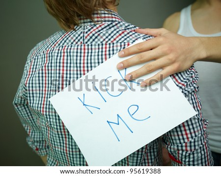 Guy being unaware of a �Kick me� sign attached to his back