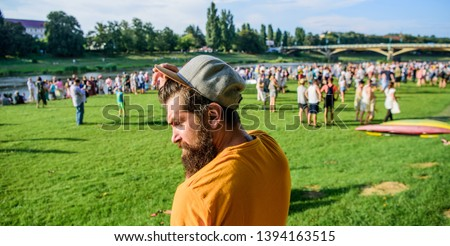 Guy celebrate holiday or festival. Summer fest. Man bearded hipster in front of crowd. Book ticket now. Open air concert. City day. Music festival. Entertainment concept. Visit summer festival.