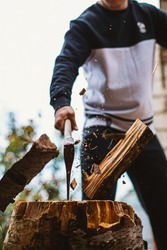 Guy chopping wood with an ax.