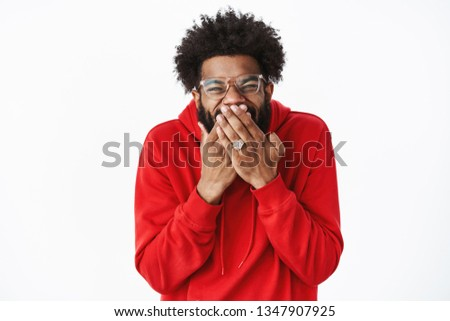 Guy chuckling and giggling as trick friend, made prank standing delighted after scheming evil plan covering mouth and squinting from joy and satisfaction, posing happy over gray background Сток-фото ©