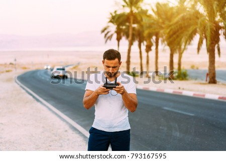 Guy controls drone with remote control, desert #793167595