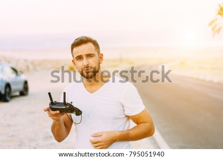 Guy controls drone with remote control, desert #795051940