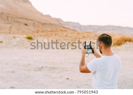 Guy controls drone with remote control, desert #795051943