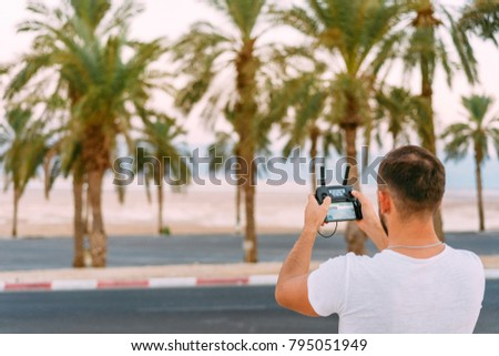 Guy controls drone with remote control, desert #795051949