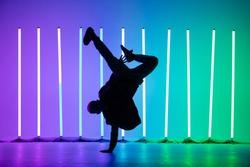 Guy dancing contemporary dance in studio. Neon light tube background. Acrobatic bboy dancer. Break dance lessons.