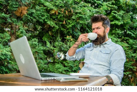 Guy drinks coffee relaxing terrace branches background. Man bearded hipster make pause for drink coffee and relax while sit with laptop. Aroma cappuccino. Pleasant moment. Take moment to enjoy life. #1164121018