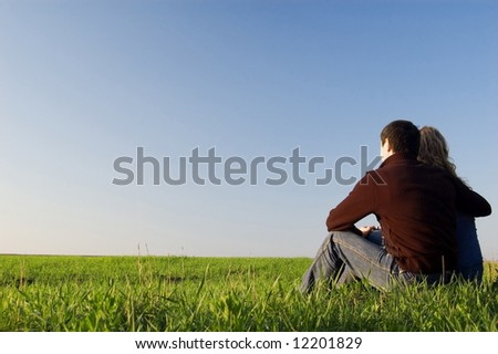 guy embraces girl on a spring field. Low foreshortening