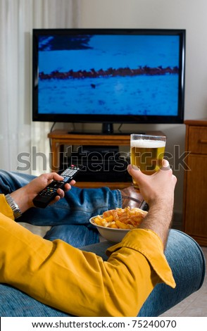 Guy enjoying his evening watching television from the sofa