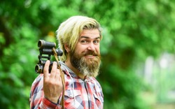 Guy explore environment. Man ornithology expedition in forest. Man observing nature. Hipster tourist holds binoculars nature background. Tourism summer vacation. Hobby and leisure. Observing nature.