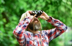 Guy explore environment. Tourism summer vacation. Hobby and leisure. Observing nature. Man ornithology expedition in forest. Man observing nature. Hipster tourist holds binoculars nature background.