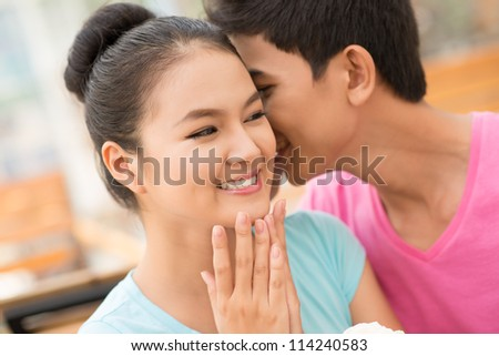 Guy flirting with his girlfriend whispering in her ear with tenderness