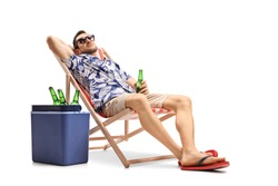 Guy holding a bottle of beer on a deckchair with a cooling box beside isolated on white background