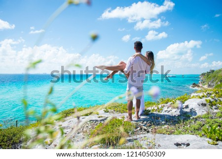 Guy holding his wife or girlfriend on hands, they both look at the turquoise water of caribbean sea. Romantic concept. Honey moon concept.