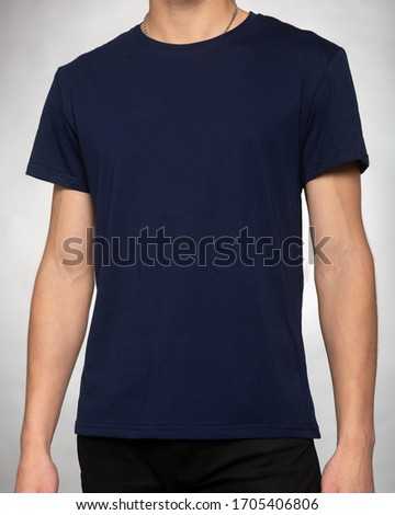 guy in a dark blue plain t-shirt clothes stands with his hands down on a light gray background Photo stock ©