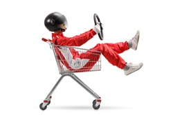 Guy in a racing suit with helmet holding a steering wheel and sitting inside a shopping cart isolated on white background