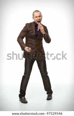 Guy in a suit with a microphone sings