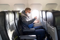 Guy in airplane, young man in glasses, medical protective sterile mask on his face sitting on plane using, apply sanitizer for disinfect hands against coronavirus, virus bacteria. Pandemic covid-19