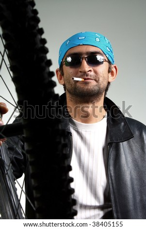 guy in dark glasses with a bicycle wheel - stock photo