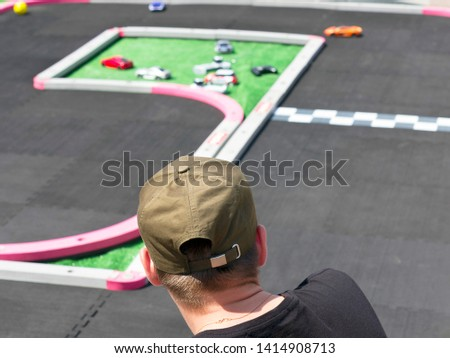 Guy in Green Baseball Cap and Black T-Shirt Watches Toy Remote Control Racing Cars on Track at the Event. #1414908713