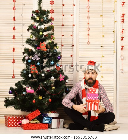 Guy in hat and scarf sits by Christmas tree and presents. Festivals and gift concept. Santa Claus with surprised face on wooden wall and red garlands background. Man with beard holds present boxes