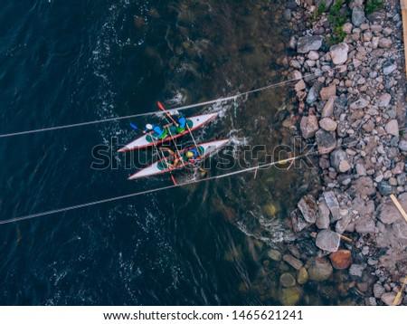 Guy in kayak sails mountain river. Whitewater kayaking, extreme sport rafting. Aerial top view.