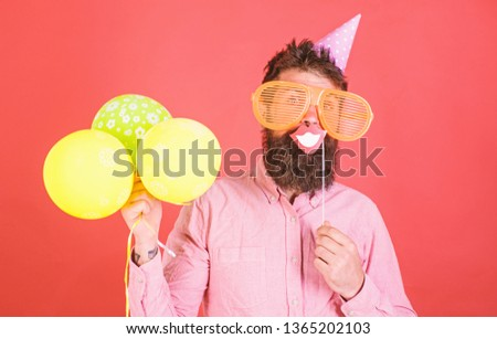Guy in party hat with air balloons celebrates. Hipster in giant sunglasses celebrating. Man with beard on cheerful face holds smiling mouth on stick, red background. Photo booth fun concept. #1365202103