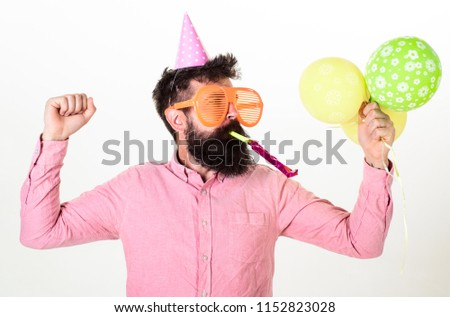 Guy in party hat with air balloons celebrates. Man with beard and mustache on busy face blows into party horn, white background. Hipster in giant sunglasses celebrating birthday. Celebration concept.