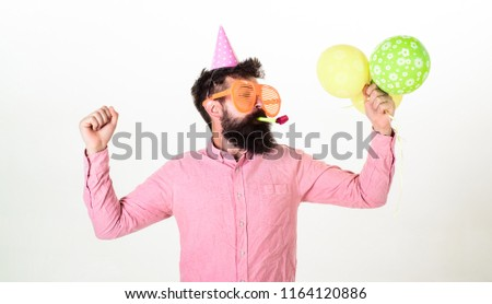 Guy in party hat with air balloons celebrates. Man with beard and mustache on busy face blows into party horn, white background. Celebration concept. Hipster in giant sunglasses celebrating birthday. #1164120886