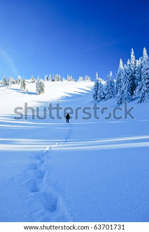 Guy in the distance and line of his footprints in frozen country