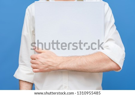guy in white shirt, man holds a mockup of blank square template, book template, front view, background, copy space, for advertising, slogan, text, blue background #1310955485