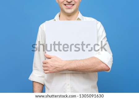 guy in white shirt smiling, man holds a mockup of blank square template, book template, front view, background, copy space, for advertising, slogan, text, blue background #1305091630