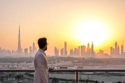 Guy in white suit looking at glowing sunset over the skyline of Dubai. Luxury travel inspiration.