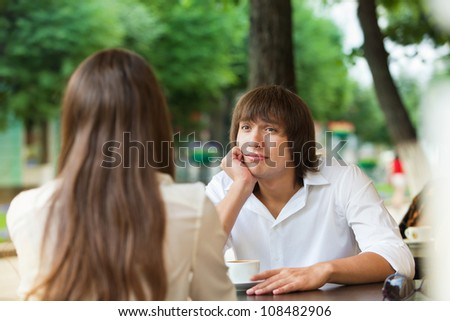 guy is bored on a date with a girl in a summer cafe