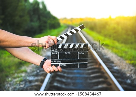 Photo of  Guy is holding black clapperboard in hands. Man is directing and filming some amateur cinema movie. Rail trails on the background, Travel concept.