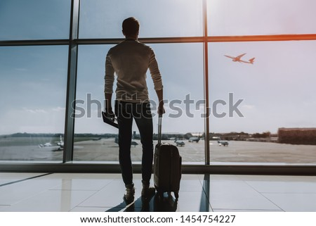 Guy is standing near big window at airport. He is looking outside and observing transport. Copy space in right side