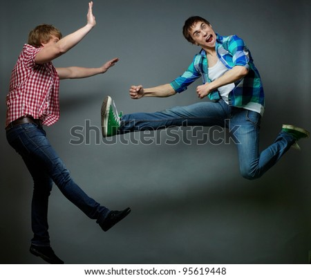 Guy jumping into air and kicking his friend, fool�s day series