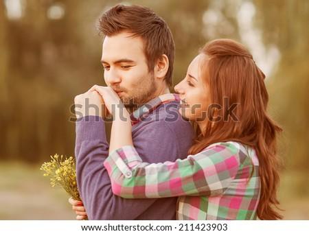 guy kisses the girl\'s hand in park