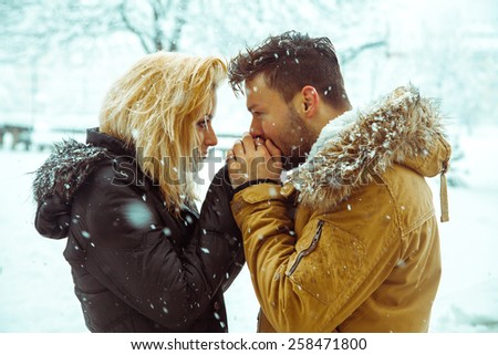 guy kisses the hand of a lady in the snow. horizontal color photo