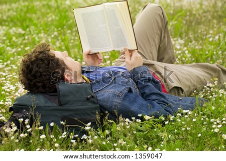 guy laying on the grass and reading a book