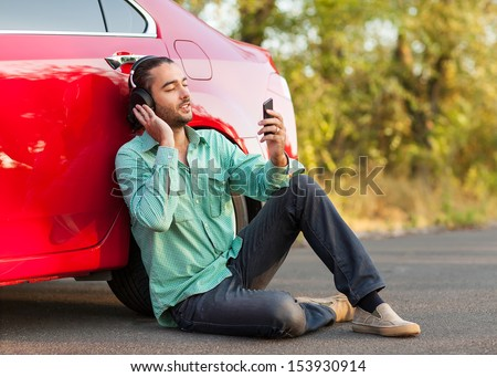 guy listening to music while sitting beside the car on the road
