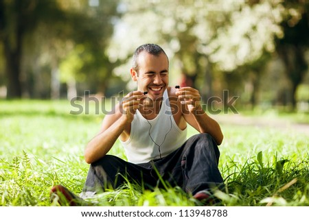 guy listening to the player sitting on the grass