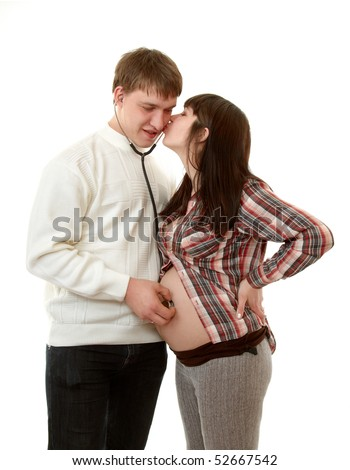 stock photo : guy listens to a stethoscope belly pregnant girl, ...