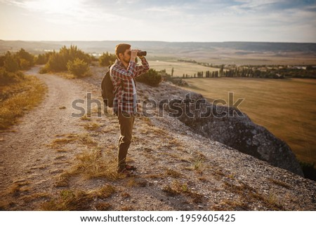 Guy looking at binoculars in hill. man in t-shirt with backpack. Young Caucasian man during hike in valley landscape