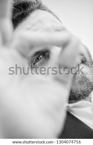 Guy looks suspicious through ok gesture close up. Excellent concept. Spying watching and observing. Man bearded businessman formal suit watching through fingers. I am watching you. Perfect gesture.